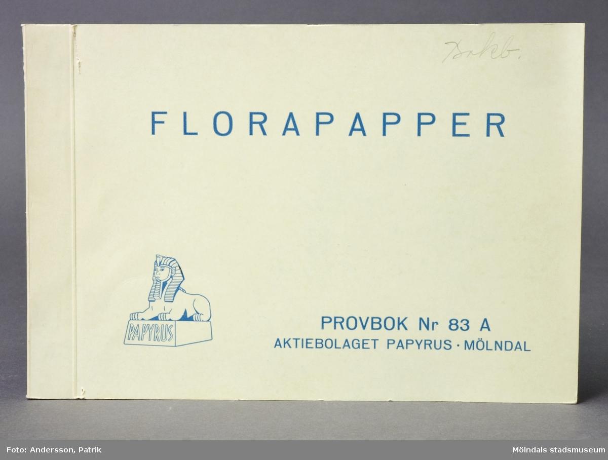 """Provbok Nr 83A. Häfte med Florapapper. Pärm av grönt papper och tryckt blå text. En handskriven anteckning i blyerts, """"Bokb"""". Papyrus logotyp, sfinx på fundament, och tillverkarnamn. 34 st ihopvikta provark i olika färger och motiv. Varje ark är numrerad. Litteratur: Papyrus 1895-1945, Minnesskrifter, Esseltes Göteborgsindustrier AB, Göteborg 1945."""
