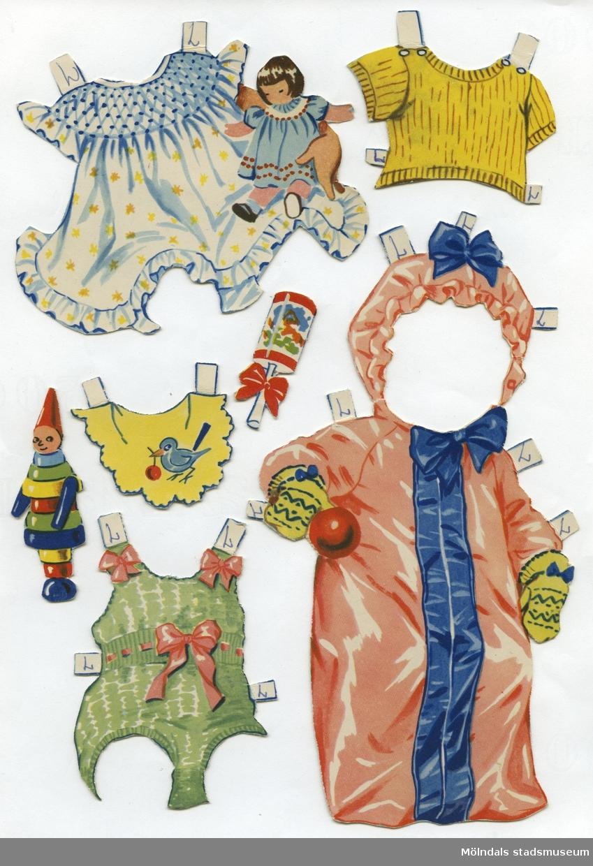 """Pappdocka med kläder och tillbehör. Docka och kläder är märkta """"Lillan"""" på baksidan - dockans namn. Dockan föreställer en baby, med blont hår och blå ögon, iklädd rosettprydda underbyxor. Garderoben består av en liten tröja, tre lekdräkter, tre klänningar, skor, mössor, samt ytterkläder. Dockan har också tillbehör, såsom potta, hårborste och leksaker. Dockan förvaras, tillsammans med """"Lena"""" (MM 04636), i ett ihopvikt silkespapper med texten """"Ljungsko, Kvalitetsko""""."""