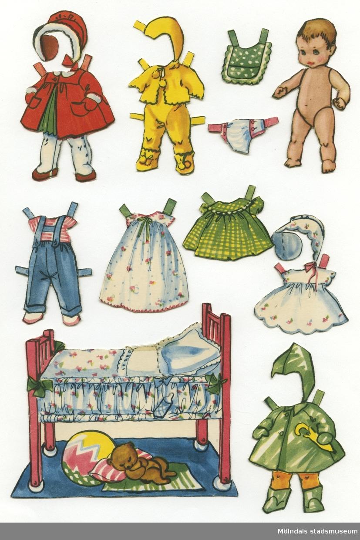 """Pappdocka med kläder och tillbehör från 1950-talet. Docka och kläder är märkta """"Åsa"""" på baksidan - dockans namn. Denna docka är i sin tur """"leksak åt en annan pappdocka"""", """"Cristina"""" (MM 04661).Pappdockan föreställer en naken babydocka. Garderoben består av två klänningar, två byxset, dopklänning, samt två set med ytterplagg. I materialet finns också tillbehör, såsom hakklapp, tygblöja och säng. Docka med kläder och tillbehör förvaras i ett brunt kuvert, tillsammans med """"Cristina"""" (MM 04661), ursprungligen från Uppbördsverket, Göteborg (Skatteverket)."""