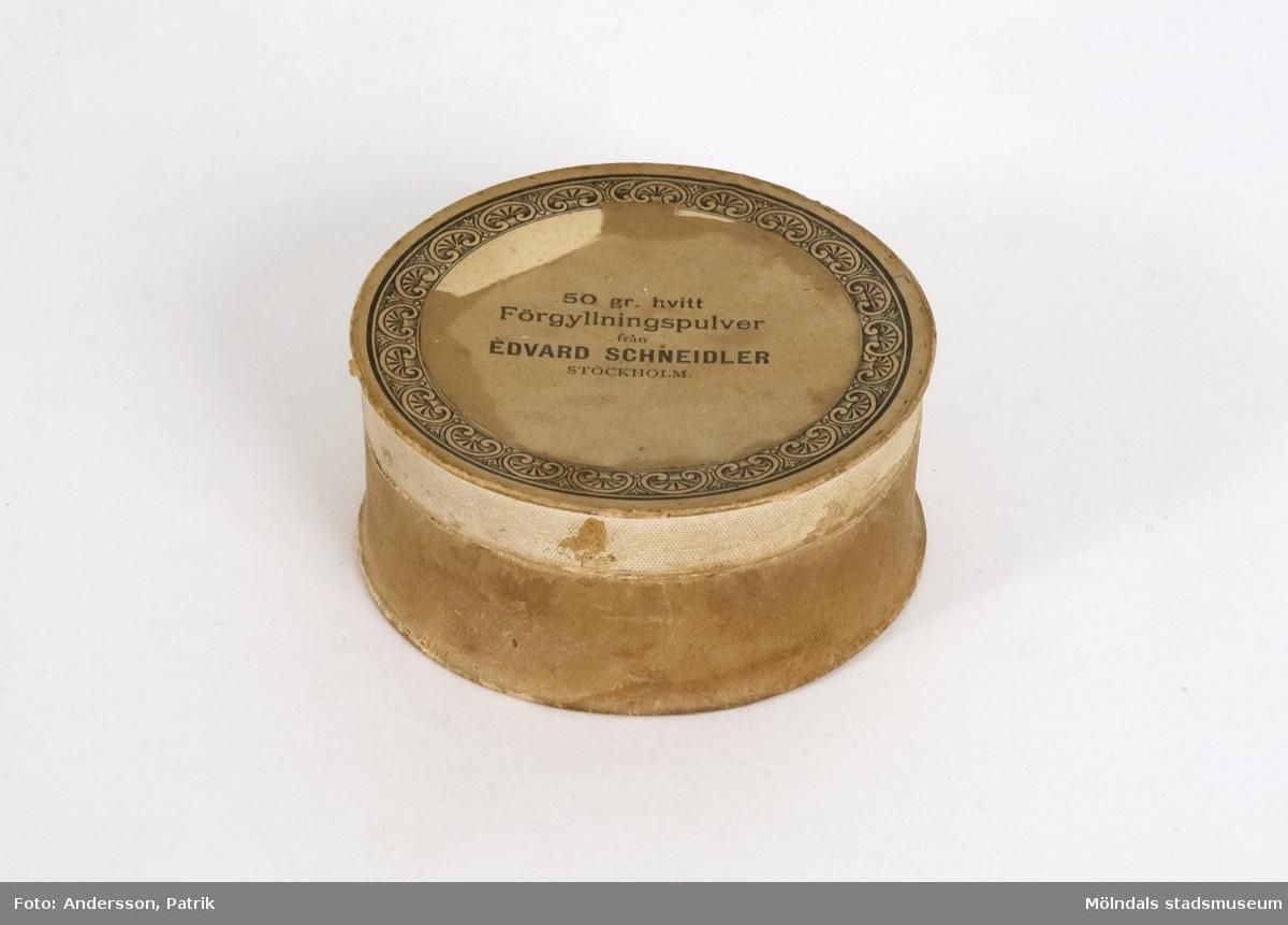 """Vitt förgyllningspulver i pappask, som använts på Papyrus, eventuellt från början av 1900-talet. Text på asken: """"50 gr. hvitt Förgyllningspulver från EDVARD SCHNEIDLER, Stockholm"""". Runt kanten på locket; stiliserad blombård."""