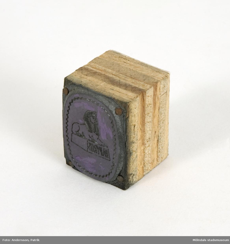 """Trycktyp av metall, monterad på träkloss, från Papyrus. Märkt """"Kromo 2/60"""". Motivet på typen är Papyrus logotyp med sfinx på fundament.Motivet är spegelvänt för att det skall överföras rättvänt vid tryck på papper."""
