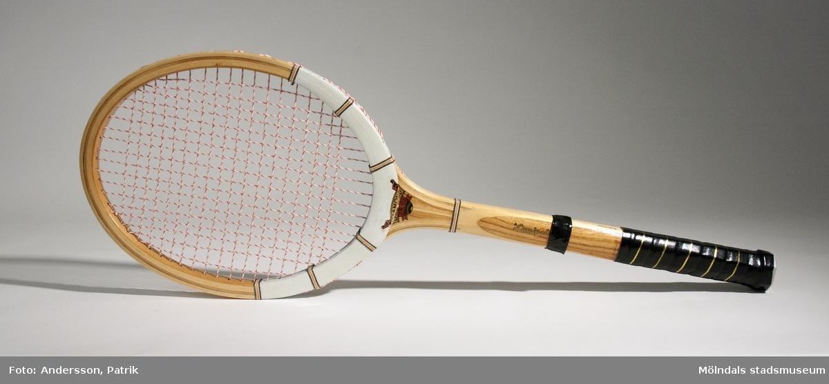 """Oanvändt tennisracket från 1970-talet.Racket är av trä. Nedre delen av skaftet är tejpat för att få ett bättre grepp. Skaftet har också målad text på båda sidor: """"DIAMOND SUPER"""" och """"A Laminated Construction"""". I endan av skaftet sitter en plastplugg där texten """"MADE IN PAKISTAN"""" tryckt.MåttNätet: 240 mm x 310 mm, Höjd: 17 mm,  Längd med skaft: 686 mm, Längd på skaft: 377 mm, Diam på skaft: ca. 35mm."""