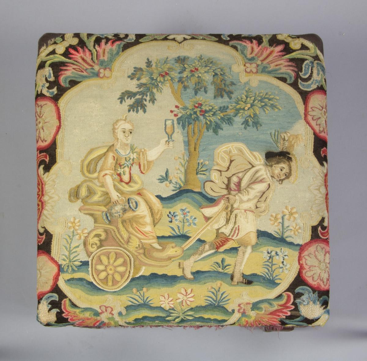 Stolsbeklädnad från 1700-talets början, flamskväv (gobelinteknik) med ullgarn och silkegarn i många färger på lingarnsvarp. Motiv: man med hatt drar en liten kärra i vilken sitter en finklädd kvinna. Hon håller i ett vinglas och en kanna. I bakgrunden ett träd med frukter, på marken blommor. Bård med blomsterornament. Enligt NM:s bedömning är motivet troligen efter Le Brun och kan eventuellt vara en fruktbarhetsgudinna.  Monterad på taburett, SKANM.0186097 B.