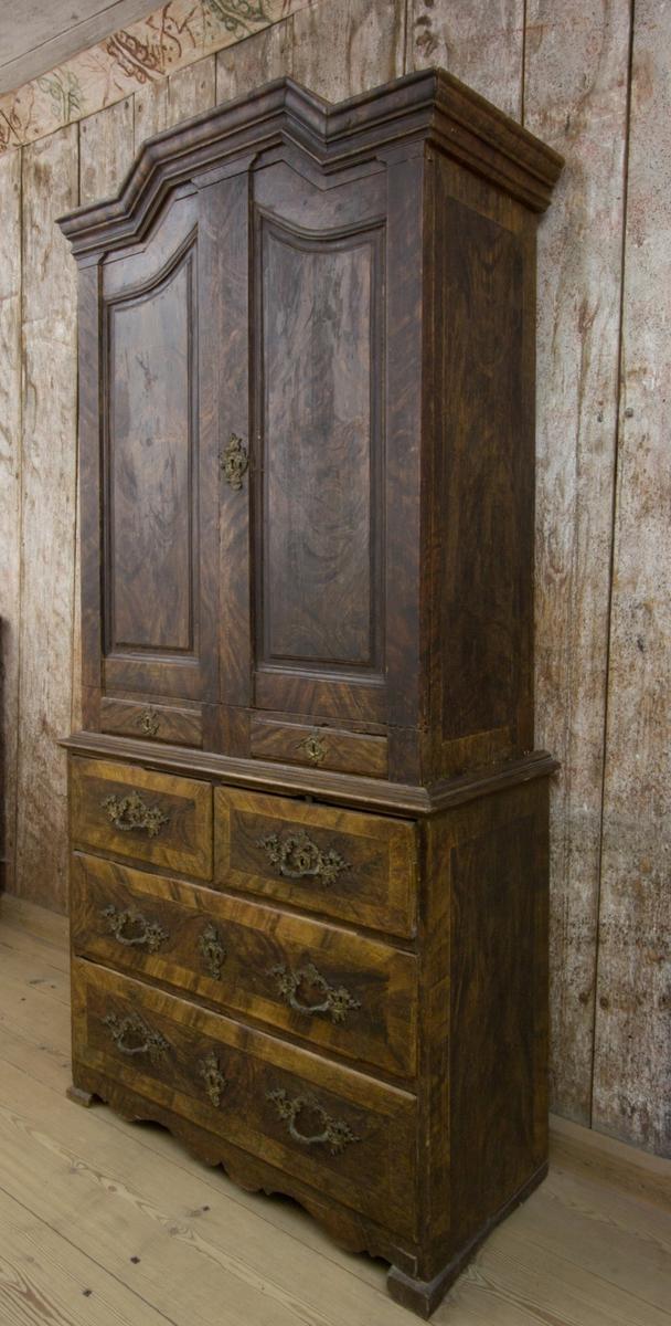 Skåp, skänkskåp, rokoko, med uppdraget brutet krön och undergehäng. Målat med ådringsmåleri efterliknande valnötsfaner. Överdelen, invändigt målat i rött, med två låga lådor, två hyllor samt en skedhylla bakom två skåpsdörrar. Underdelen med fyra draglådor, varav de två översta bredvid varandra. Lådor och dörrar med brännförgyllda beslag och draghandtag.