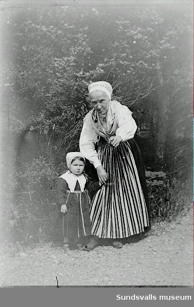 Porträtt. Kvinna med barn klädd i folkdräkter i utemiljö.