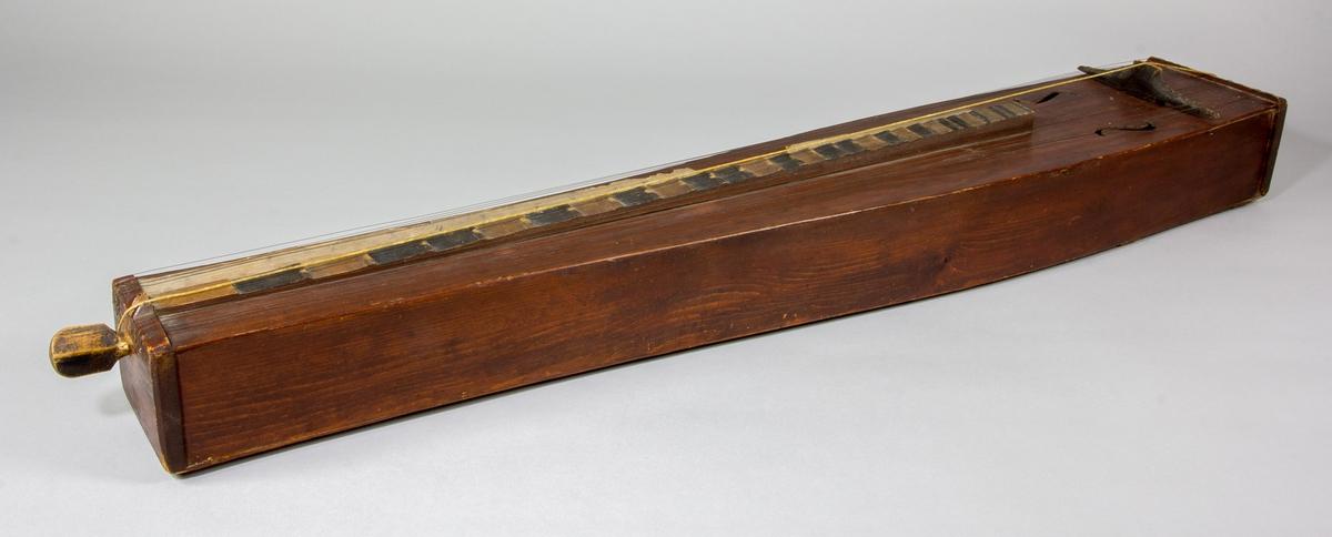 Psalmodikon från Nöbbele, Småland, från c:a 1850. Låda av trä med en sträng, plats för 12 bordunsträngar. Lätt utsvängda sidor, S-formade ljudhål. En remsa av papp med siffror för notlägen monterad på ena sidan om tonbrädan.