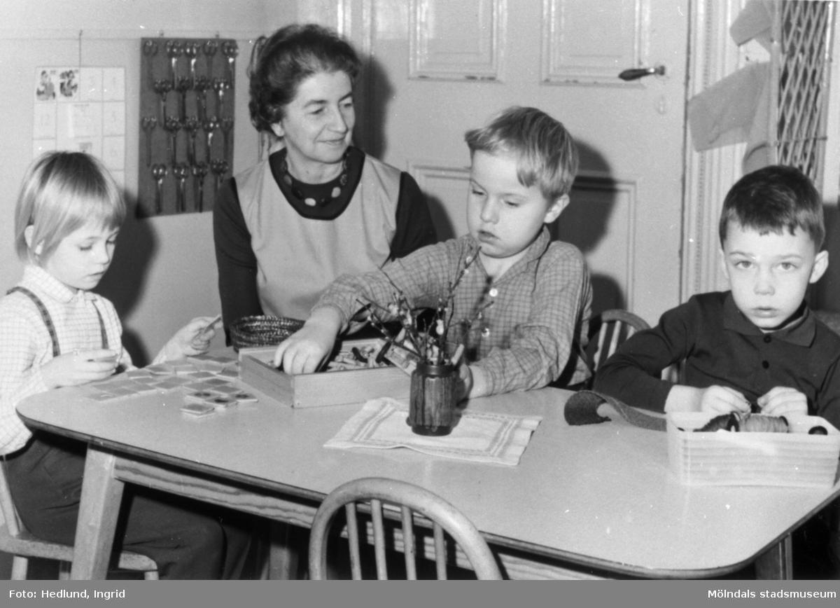 Bosgårdens barnträdgård 1938-1945. Lärare och barn som sitter och pysslar vid ett bord.
