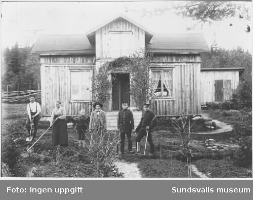 Familjegrupp, som håller på med trädgårdsskötsel. Gammalt bostadshus i bakgrunden.