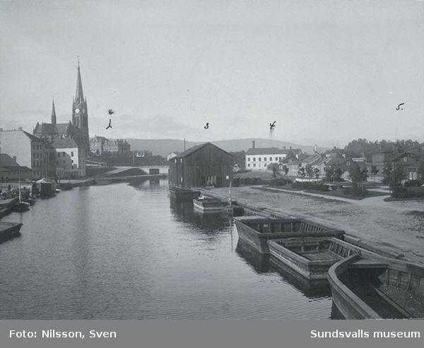 Från vänster Gustav Adolfskyrkan, Storbron och till höger Centralbryggeriet. I förgrunden bruksbåtar och magasin efter Selångersån. Bilden är tagen från öster.