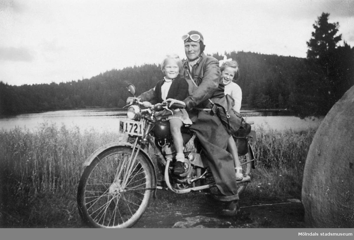 Arvid Svensson har en lättviktare model 98cc Rex, som han tar sig till jobbet med, vid hemresan tar han upp barnen på åktur, 1949. Då räckte en skinnluva som skydd för huvudet. Margareta Nordin var sommargäst på Långö.