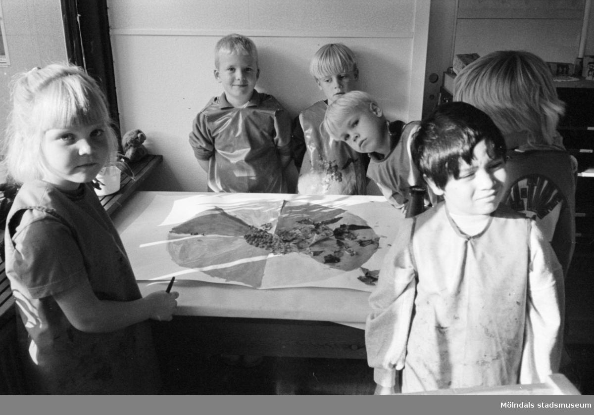 Sex dagisbarn, stående runt ett bord, som gemensamt har målat/ritat en stor teckning. Katrinebergs daghem, 1992-93.