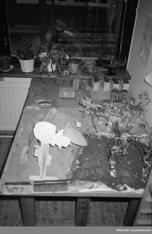 Dagisbarnen vid Katrinebergs daghem har gjort flera utomhusmiljöer i miniformat genom att skapa hus, träd osv. Här ser man fyra varianter ståendes på ett träbord, fotograferat från annan vinkel än foto: 1993_0836.