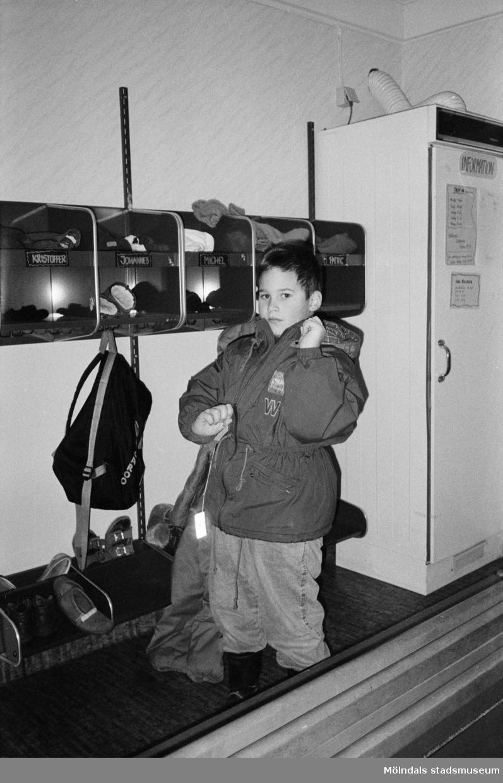 Johannes drar ner dragkedjan på sin jacka. På väggen brevid finns fack där barnen har lagt sina ombyteskläder. Entrén på Trudelutten, Katrinebergs daghem, 1992.