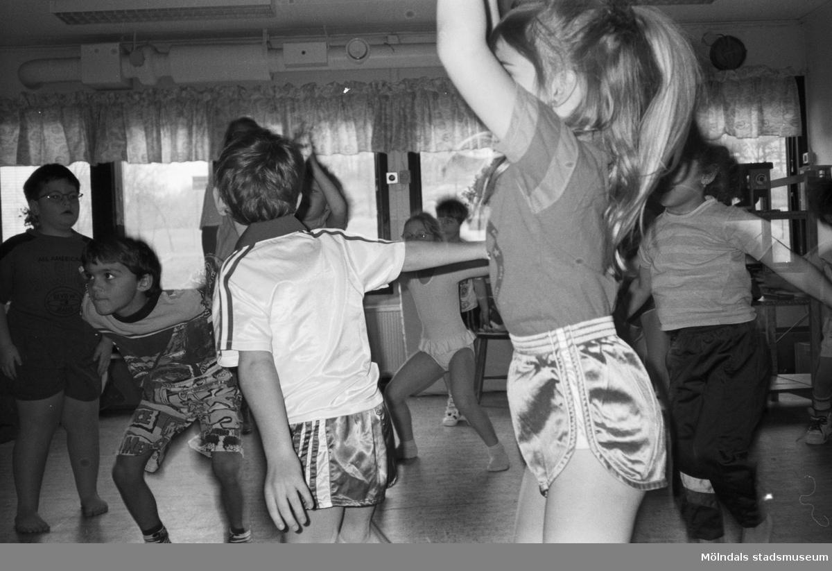 En grupp barn har gymnastik inomhus. En flicka med hästsvans hoppar framför fotografen. Katrinebergs daghem, 1992.