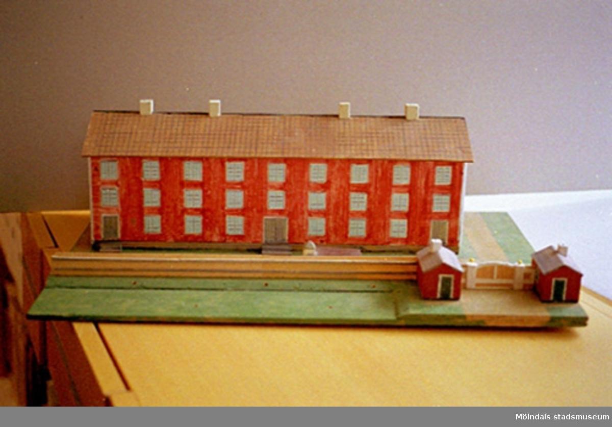 """Ett rött bostadshus med tio fönster i rad, tre våningar högt, och tre entréer. På taket finns fyra skorstenar. Vid sidan av ligger två mindre stugor. Huset är en kopia av """"Byggninga"""" som var arbetarbostäder till Anderstorps fabriker i Lindome. Se även 1994_0992-1994_0994. Harry Bergmans """"gubbar"""" (träfigurer)."""