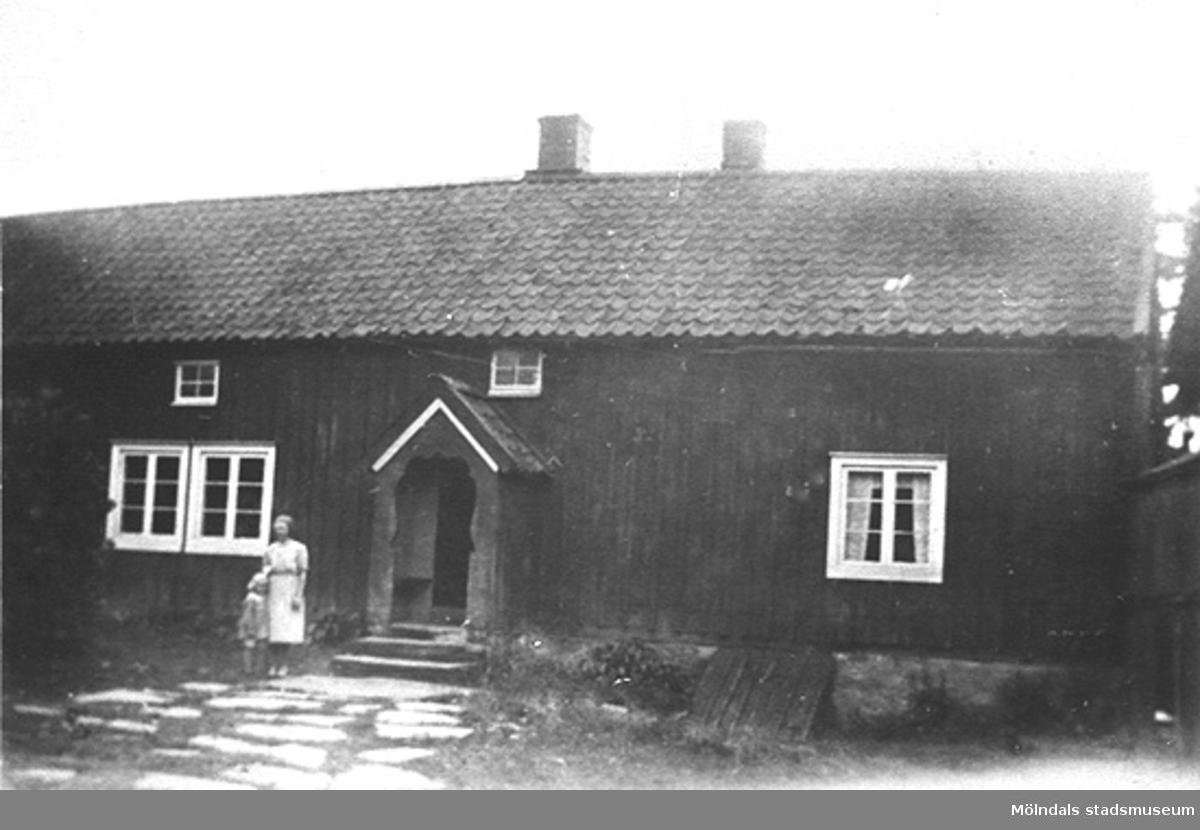 Anna Larsson (f. Hasselberg) med dottern Berit framför Salves gård, Hällesåker 4. Det var Annas mor, Clara Hasselbergs föräldrahem. Snickarverkstad fanns i byggnaden.Gården byggdes upp efter branden i Hällesåker 1830.
