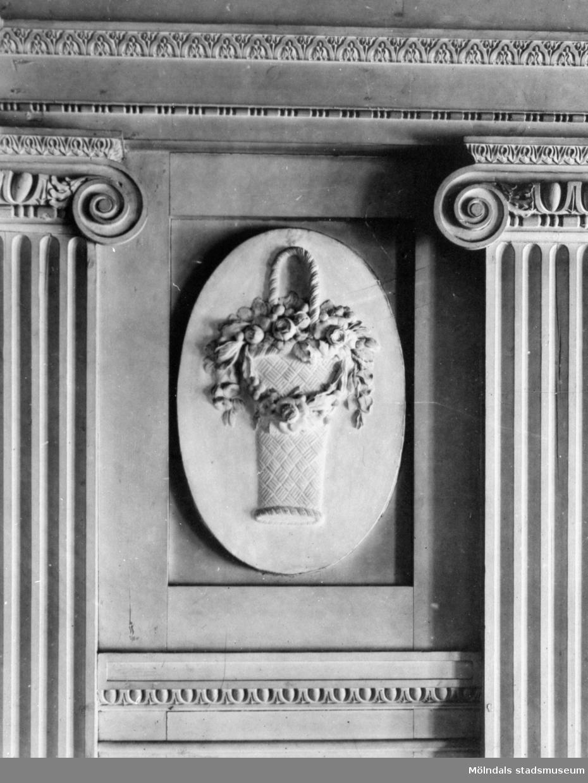 """I en tablett, en stående oval relief med emblemet """"blomsterkorg"""", placerad ovanför årstids-gipsfiguren """"Våren"""" av Gioacchino Frulli (1766-1801). Denna sitter på nordöstra väggen i stora salongen på Gunnebo slott."""