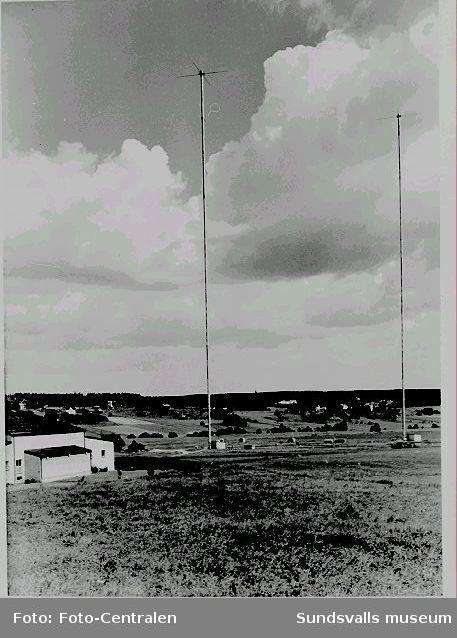 De två 222 meter höga rörmasterna, vilka togs i bruk 1953.T v rundradiostationen.