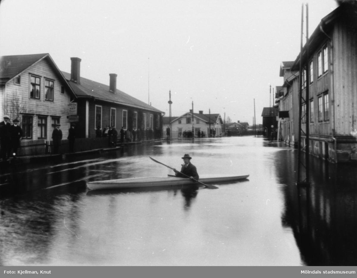 Översvämning vid Mölndalsbro, 1930-tal. Gösta Viktorinus paddlar omkring i kanot. Från vänster ses skomakare Gustaf Adolf Petterssons fastighet, spårvagnshallarna, bankhuset (Kungsbackavägen 1), Stibergs (Kungsbackavägen 2) samt Göteborgsvägen 1, 3 och 5.