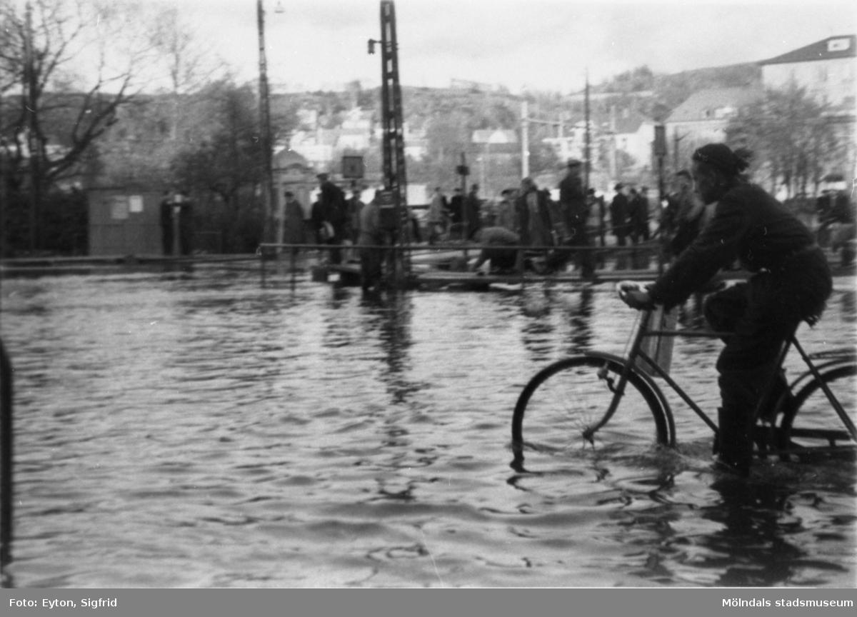 Vy mot öster, korsningen Kvarnbygatan-Frölundagatan samt Göteborgsvägen-Kungsbackavägen som är översvämmad 1951. I bakgrunden ses bron över ån, Kvarnbyskolan och biografen Röda kvarn (Kvarnbygatan 1).