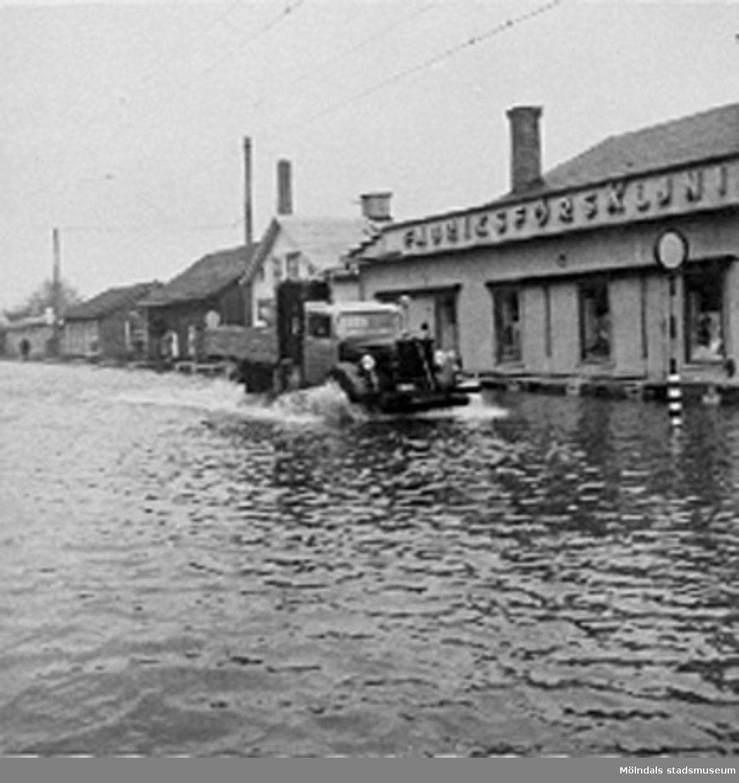 På huset t.h i bild står fabriksförsäljningen, enligt Karl är kortet taget mot spårvagnshallarna vid Mölndalsbro. Kortet är taget i samband med  översvämningen i Mölndal i februari 1943.