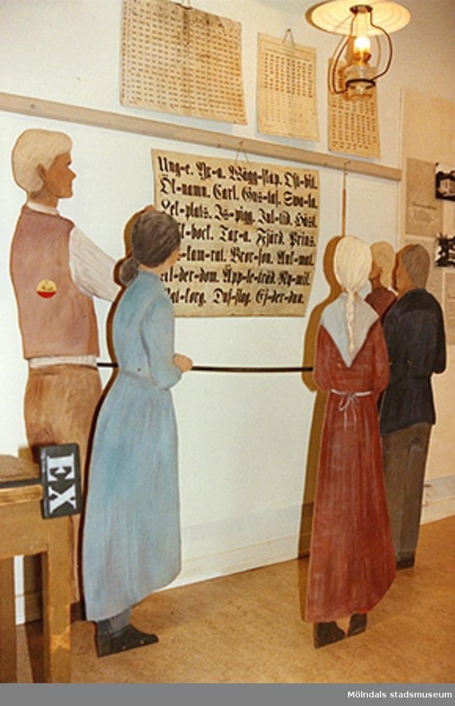 """Utställningen """"Lära för livet"""" 12 mars 1988 - 19 mars 1989 på Mölndals museum.Fem träfigurer som tittar på en bild (med text) på väggen. Detta är en läsecirkel från en Bell-Lancasterskola."""