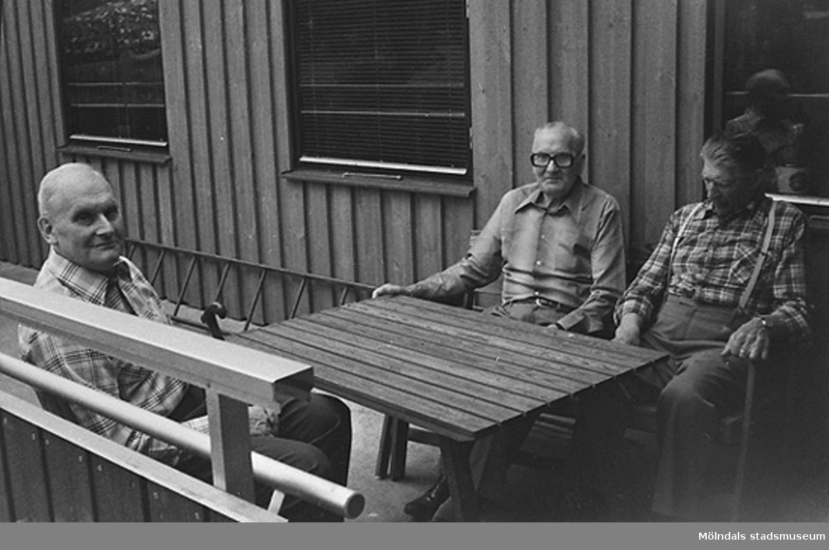 Tre män sitter utomhus på ålderdomshemmets bänkar och får lite frisk luft. Okänt årtal.