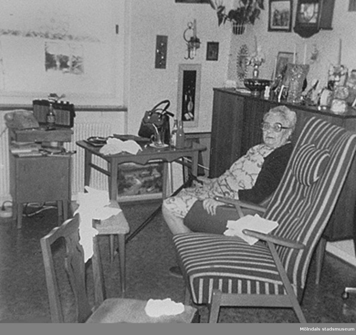 Anna Bengtsson sitter i ett rum på Brattåshemmet år 1980. Från en fotodokumentation 1985-86 av Staffan Bjerrhede och Birgitta Lans. Ålderdomshemmet Brattåshemmet låg på Brattåsvägen 3 el. 4 och var i bruk mellan 1955 och 1986.