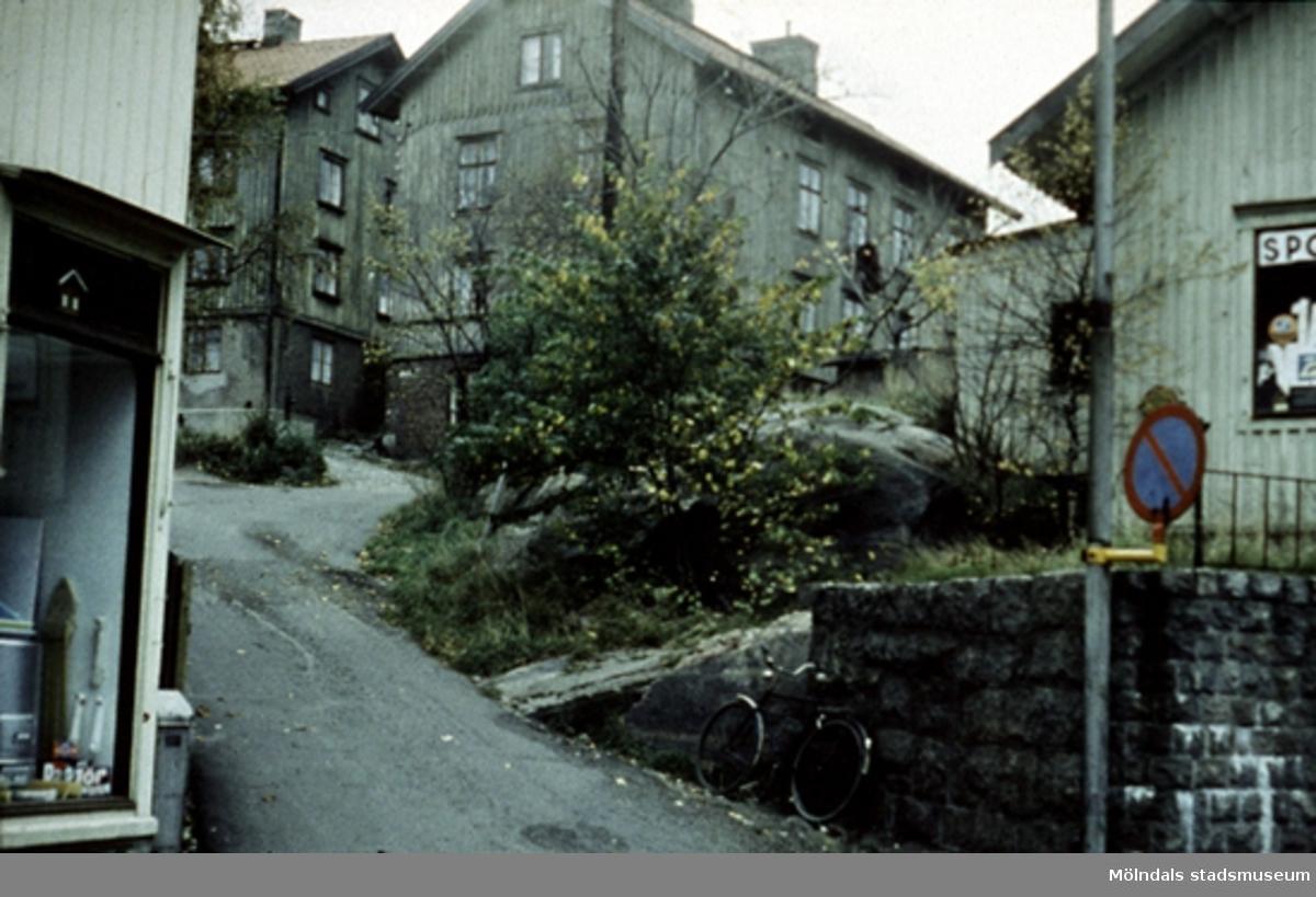 """Järnhandelsliden, mellan Kvarnbygatan 27 (Johanssons järnhandel) och Kvarnbygatan 29 (gamla Rådhuset) i Mölndals Kvarnby, våren 1962. Även kallad Smed-Kalles lid, Spanåsliden samt Röda liden. Källa: """"Mölndals gatunamn"""" av Lars Gahrn."""