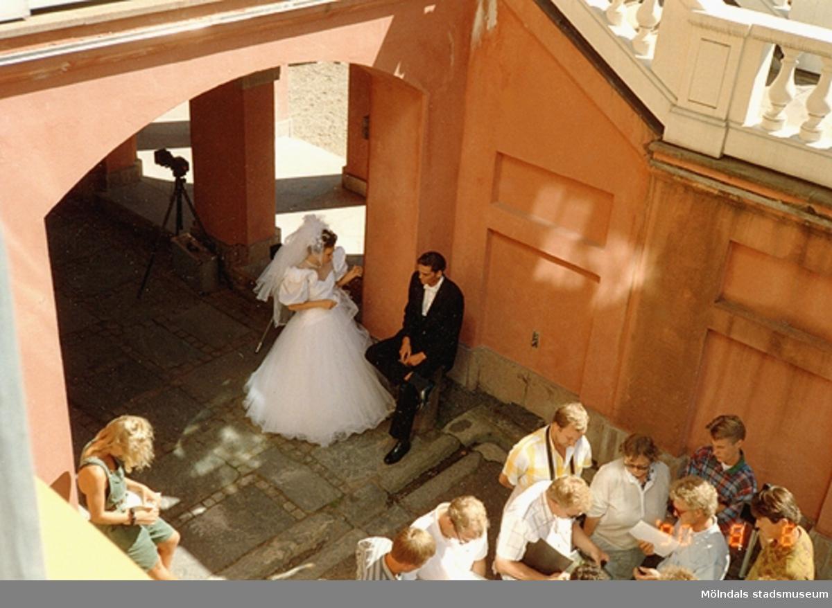Till vänster ses ett brudpar som pratar. De befinner sig i valvet nedanför Gunnebo slottsterrass. Till höger står andra personer och tittar i papper, augusti 1990. Hör ihop med: 2001_0128.