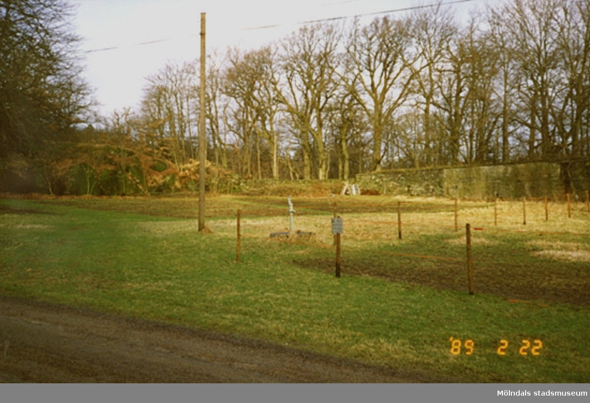 Skogsbygd och en bit av en grusväg vid en inhägnad hage. Vid hagen sitter en liten skylt. I bakgrunden ser man en stenmur.