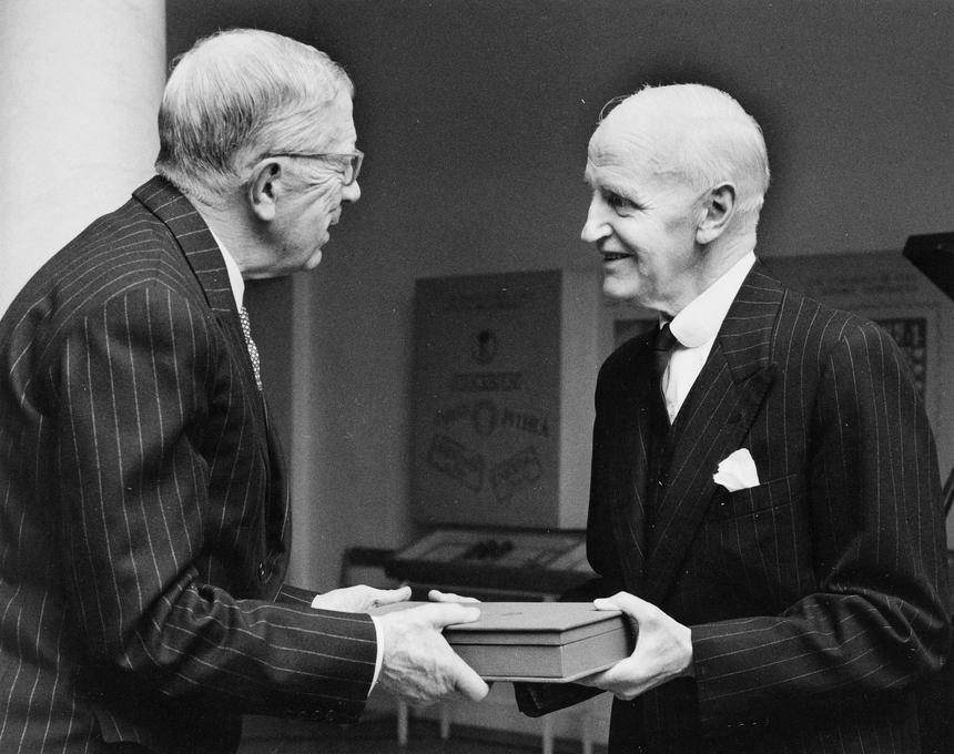 Jubileumshedersgäst var dåvarande kung Gustaf VI Adolf. Han får här mottaga en minnesgåva av ordföranden i Postmusei Vänner, ambassadör Wilhelm Winther. Gåvan består av ett album innehållande avdrag av ett stort antal frimärksgravyrer från Postens frimärkstryckeri.