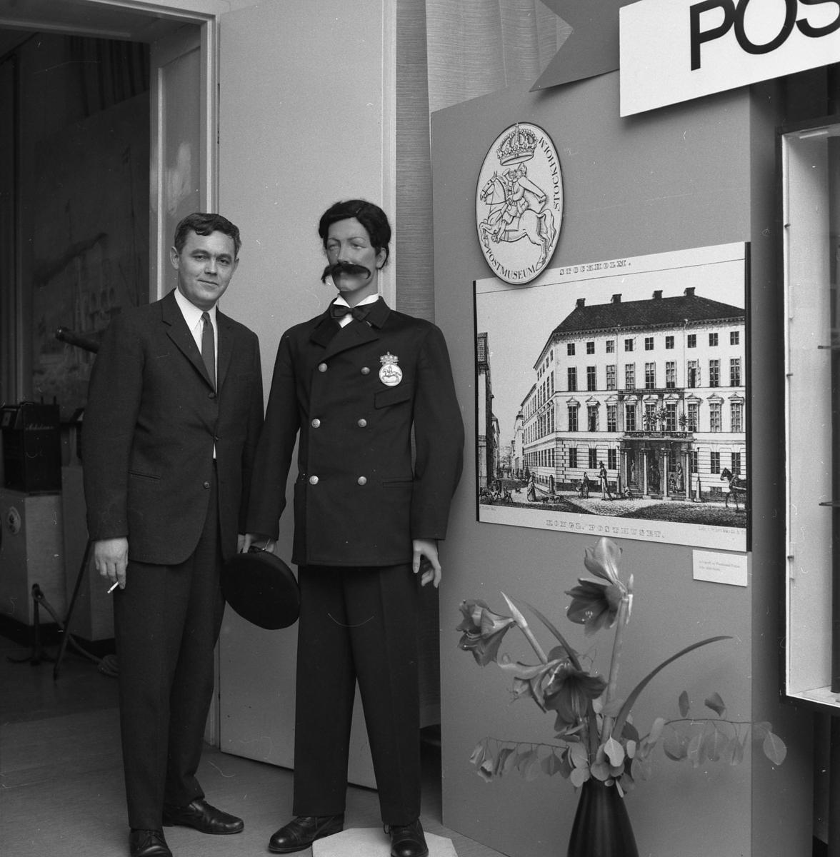 """Reklamtecknare Anders Gullberg, som komponerat utställningen """"Postmuseum 60 år"""", poserar här vid en docka i dåvarande receptionsrummet."""