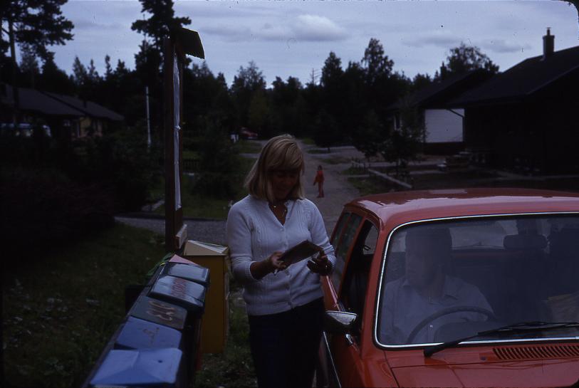 Lantbrevbärare Mikael Mattsson är i Rocksta. Han sitter i bilen och Agneta Gustavsson står utanför invid en samling postlådor och en brevlåda.