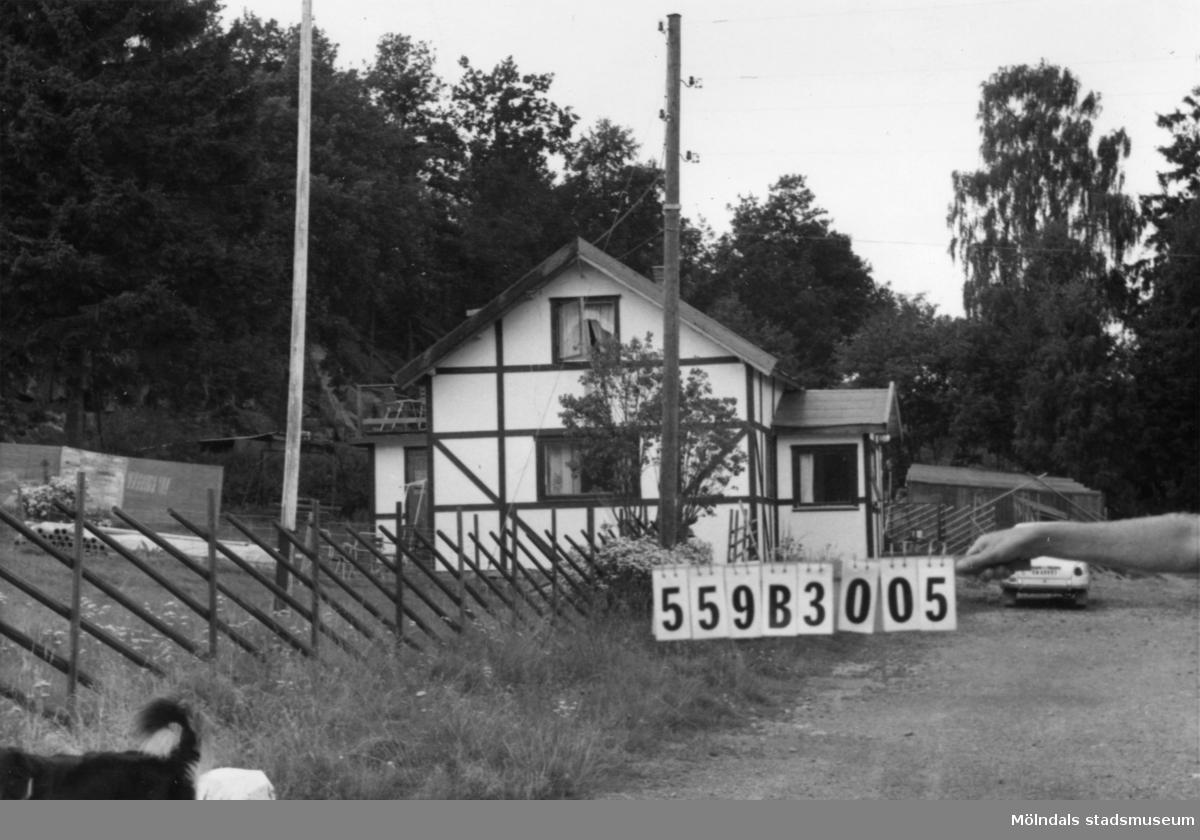 Byggnadsinventering i Lindome 1968. Torkelsbohög 1:10. Hus nr: 559B3005. Benämning: permanent bostad, ladugård och garage. Kvalitet, bostadshus och garage: god. Kvalitet, ladugård, mindre god. Material: trä. Övrigt: målat korsvirke. Inte alltför snyggt. Massor av småhus och inhängnader. Fjäderfäförädling. Tillfartsväg: framkomlig.