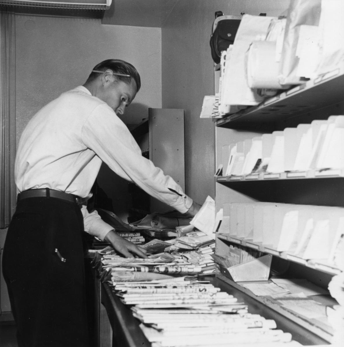 Lantbrevbärare Knut Svensson, Växjö, sorterar dagens post, 1953.