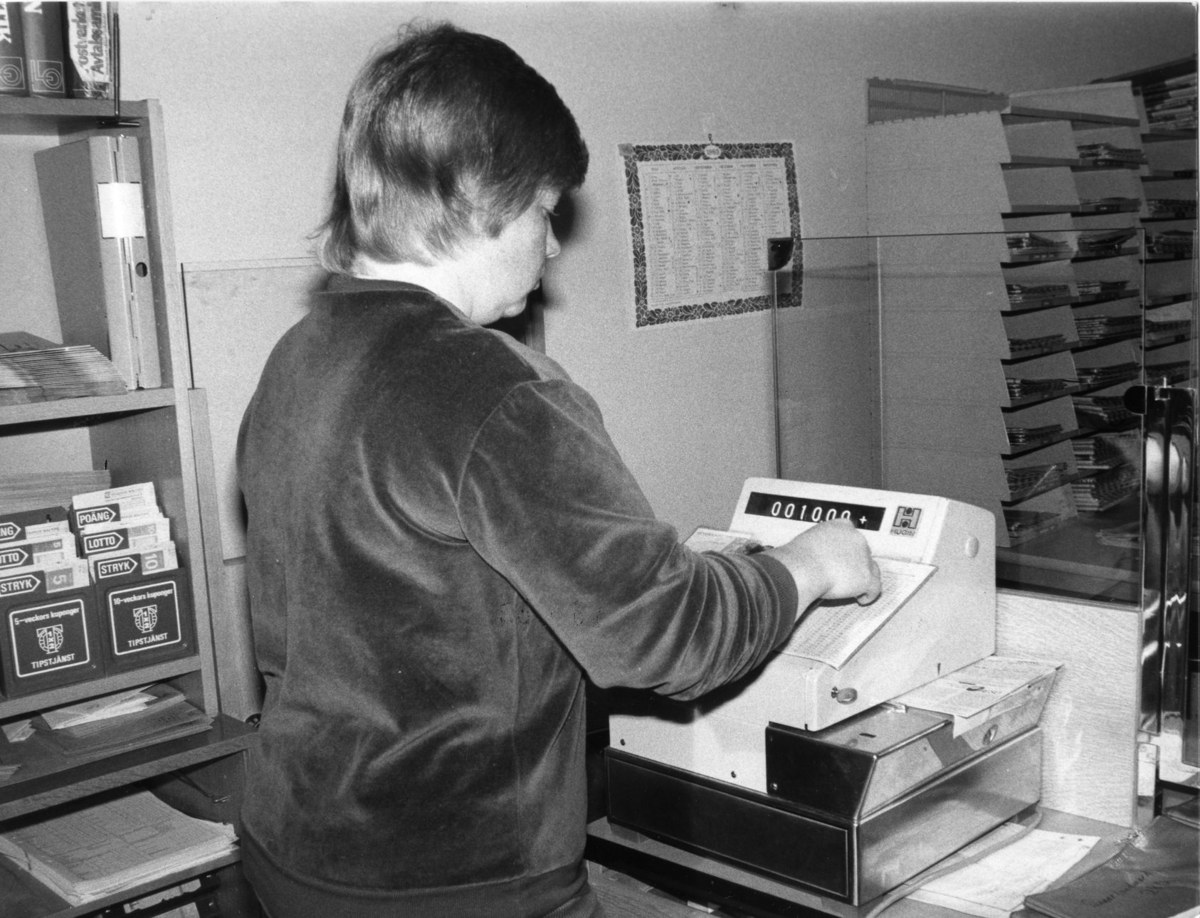 Postkassör Gerd Wikman slår in insatserna för strycktipset på den speciella kassaapparaten på postkontoret i Arvidsjaur. Ca 1983.
