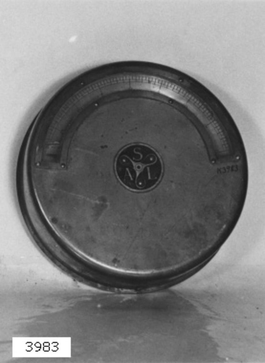 Krängningsmätare av mässing. Mätaren består av cylindrisk dosa, i vilken pendel kan svänga fritt. Pendelns rörelse överföres genom kugghjul till visare, synlig i bågböjt fönster på framsidan med skala 20-0-20. Märkt ASL mellan bladen i trebladig propeller.