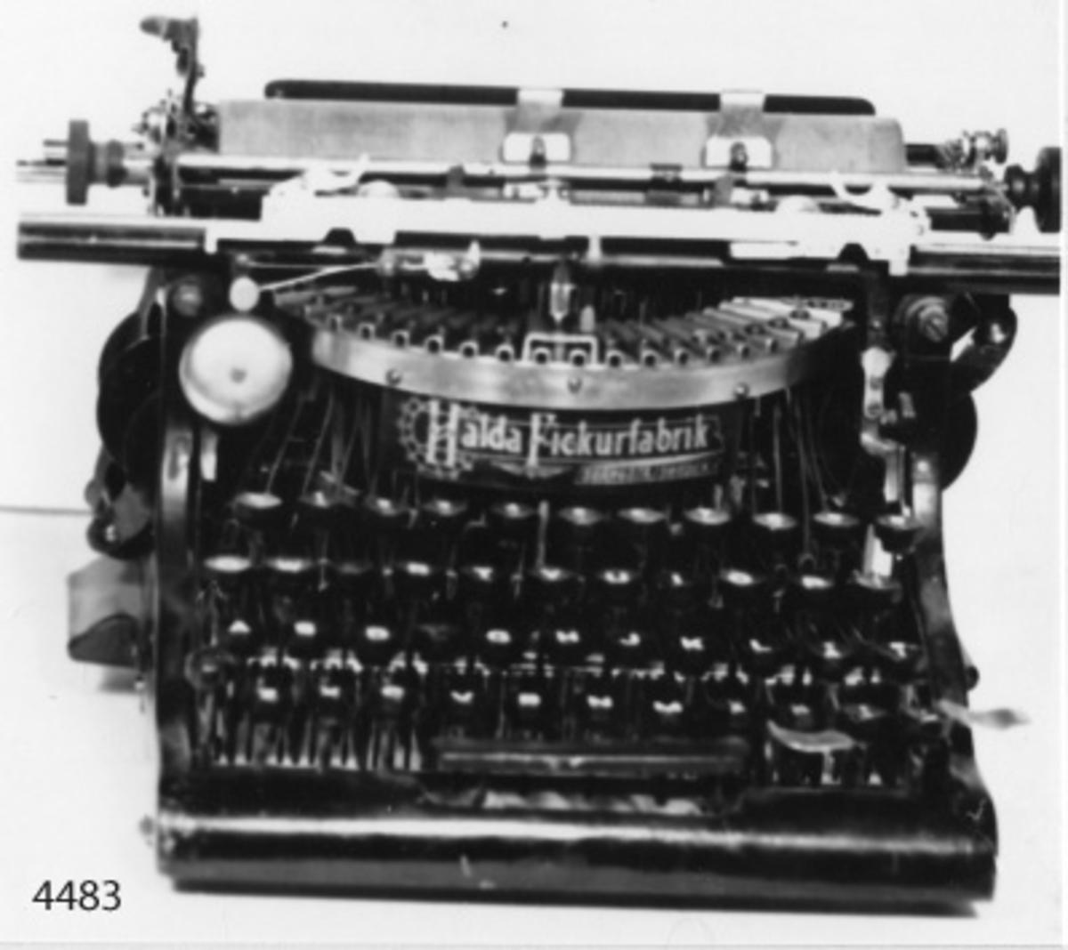 Skrivmaskin av märket Halda. Fabrikatet är svenskt, sannolikt från början av 1900-talet. Maskinen är svartlackerad och märkt i gult: Halda Fickurfabrik Svängsta (Sweden). Tangenterna är svarta med skrivtecken, siffror och bokstäver i vitt.