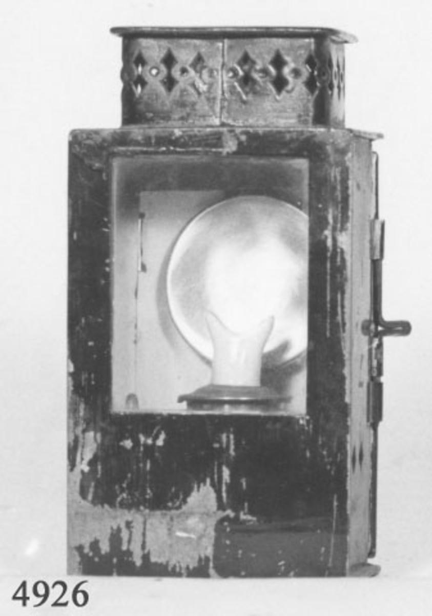 Lanterna, hand - av mässing. Rektangulär och grönmålad. Den är försedd med lampa av mässing för fotogen samt brännare av porslin. Märkning: Trade Mark Baton Patent samt på baksidan av lanternan: 20.