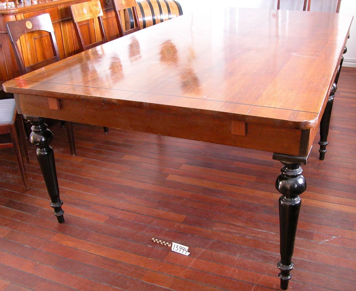 Bord, s.k. domarbord. Bordsskivan av mahogny, sex svarvade ben av björk, svarta, sargen av furuträ.