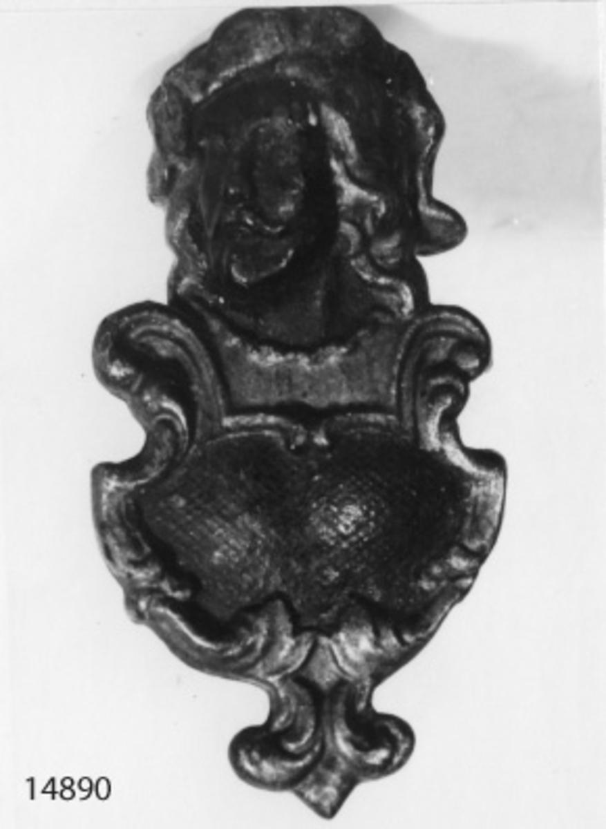 Tändstickställ av gjutjärn. Utgöres av en sköld med ett manshuvud i relief. Huvudet öppet upptill. Målat i svart och gult.