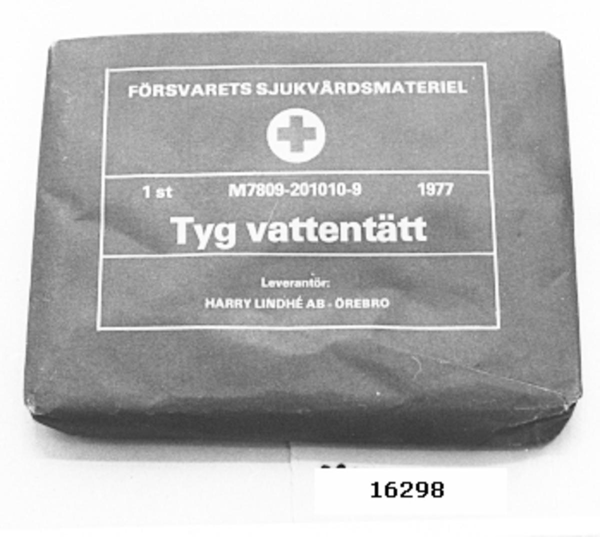 Rektangulär förpackning av mellanblått papper innehållande ihopvikt plasttyg. Tryckt text, vit, på förpackningens bredsida: FÖRSVARETS SJUKVÅRDSMATERIEL (rött kors på vit cirkelbotten). 1 st M7809-201010-9 1977. Tyg vattentätt. Leverantör HARRY LINDHÉ AB - ÖREBRO
