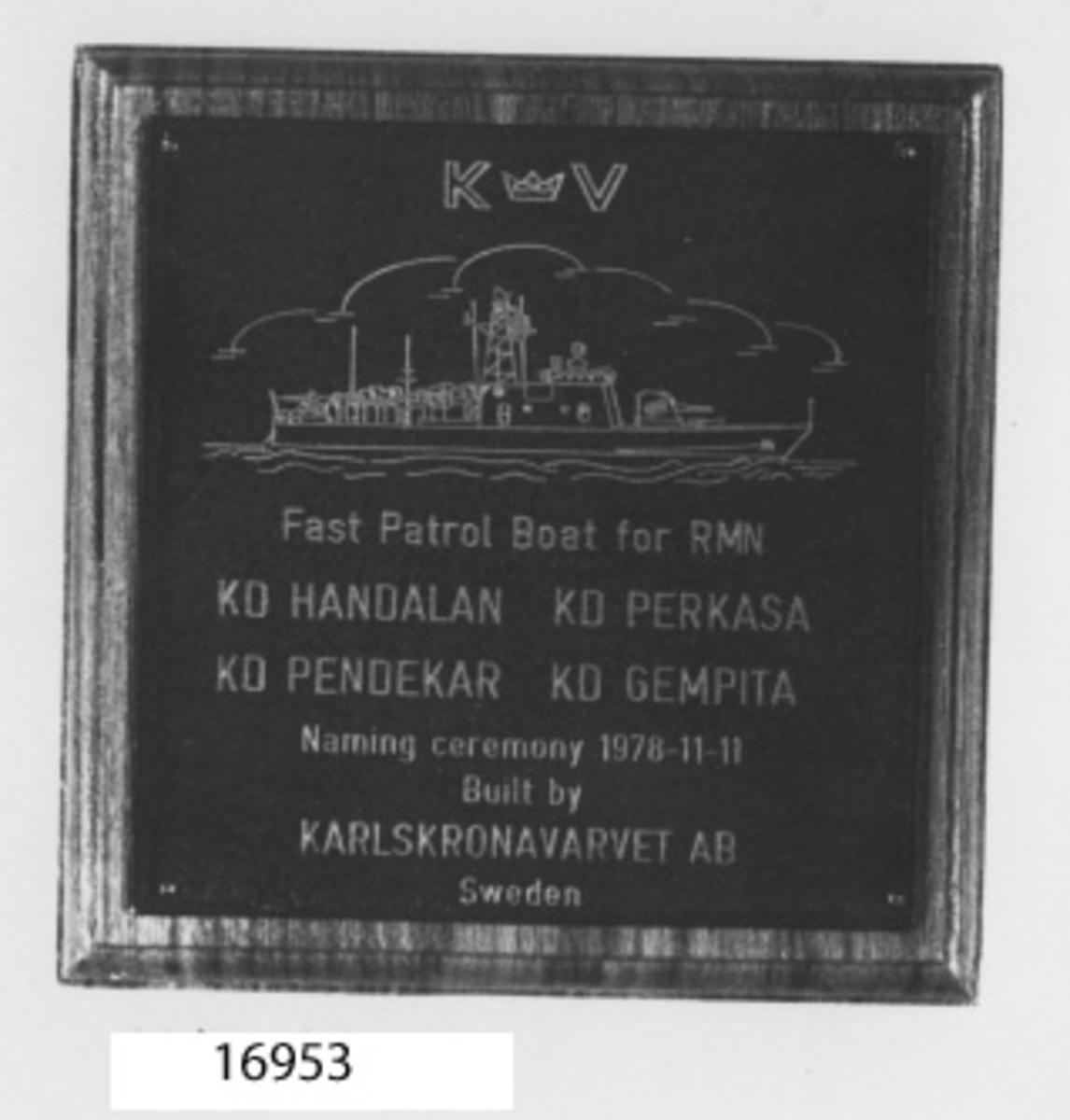 """Svartmålad metallplatta (mässing?) spikad på profilerad träplatta (teak). Graverad bild samt text i mässing= Överst K krona V, linjegravyr av patrullbåt, nedanför text """"Fast Patrol Boat for RMN, K D Handalan, K D Perkasa, K D Gempita, Naming ceremony 1978-11-11. Built by Karlskronavarvet AB Sweden."""