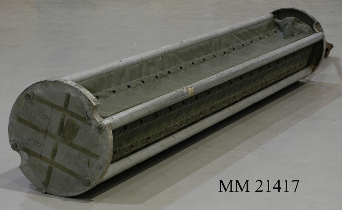 Cylindriskt föremål bestående av två runda skivor av aluminium. Mellan skivorna sitter parallella rör fästade så att en cylinder bildas, L = 2970mm. Mellan rören grön galonväv som bildar en tub. På ena långsidan är väven försedd med en dragkedja. Öljetter hela vägen längsgående, för att underlätta vatteninströmning. I ena änden vinkeljärn, rostskyddsmålade som bildas i en triangelform.