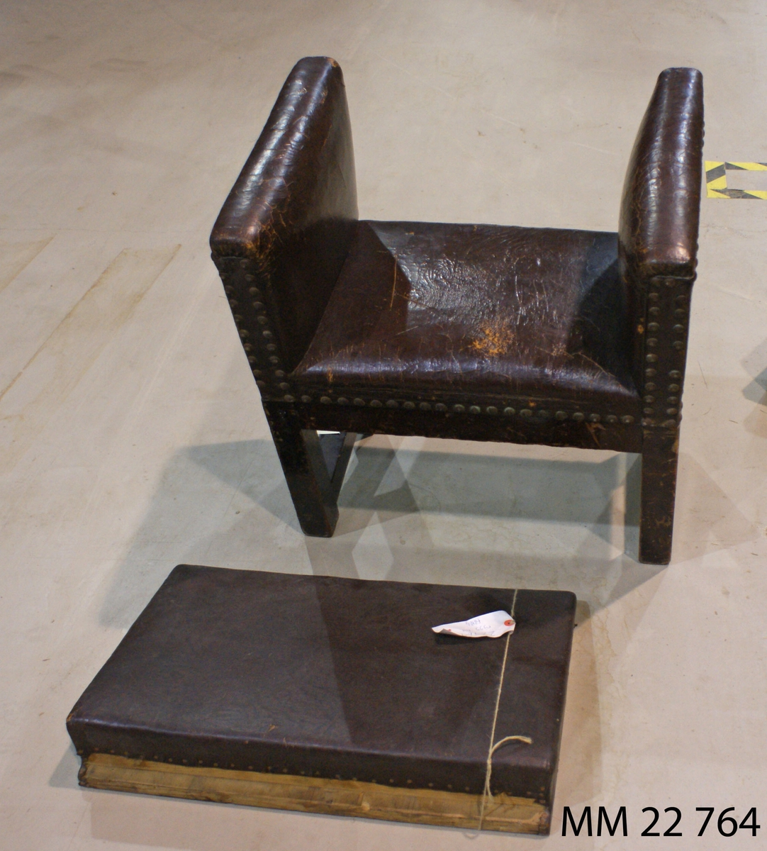 Fåtölj av svart läder på trästomme, med ryggstycke, stoppad, väggfast. :1 Fåtölj :2 Ryggstycke