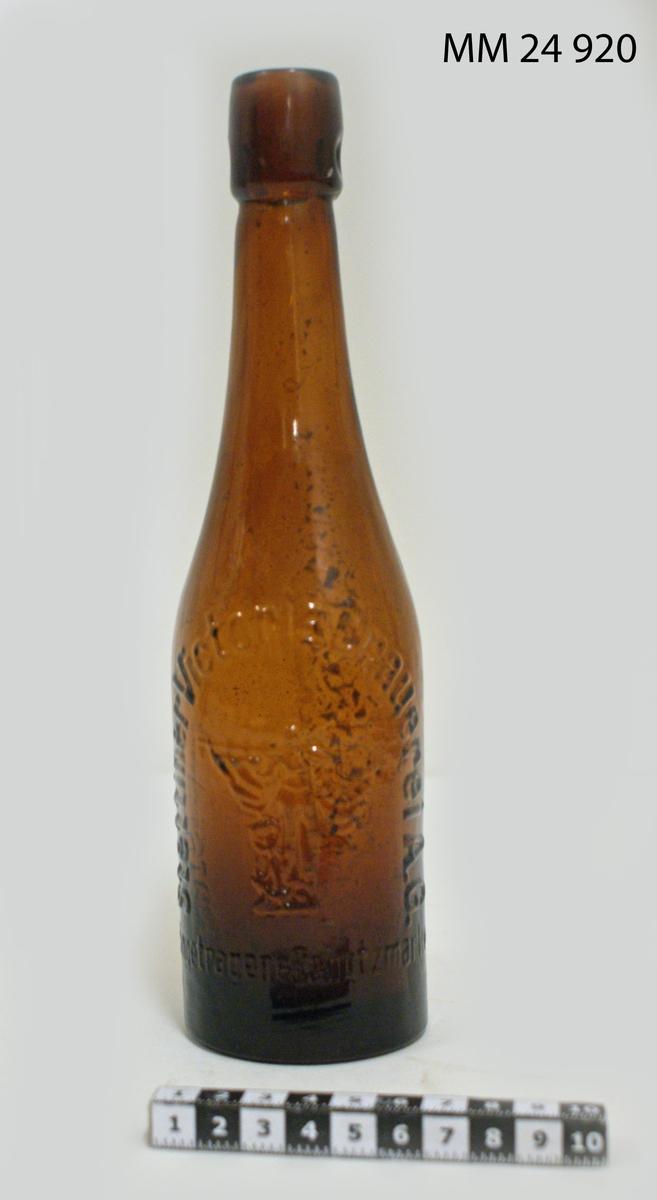 """Ölflaska av brunt glas med följande text i relief: """"Stettiner Victoria Brauerei AG. Eingetragene Schutzmarke. Unverkauflich."""" samt en kvinna med segel och ankare."""