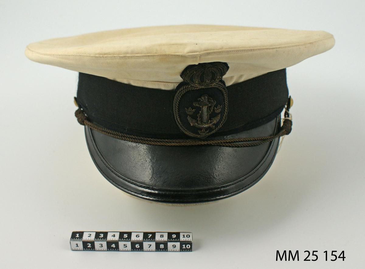 """Skärmmössa med vitt mösskapell. Mössans mellandel består av ett svart mössband med ett flaggunderofficersemblem för flottan framtill. Emblemet sytt med guldtråd. Mössremmen under mössbandet består av två snoddar som är fastsatta med en knapp på mössans sidor. Skärmen av läder med svart ovansida och grön undersida är fäst i mössans stomme. På stommens insida sitter ett brunt svettband av läder. Inuti mössan är en fyrkantig plastbit fastsydd, med text i guld: """"A-B Albert Nilsson Herrekipering Karlskrona"""". I svettbandets kant sitter en gulaktig lapp med märkningen N:o 49/935. Lapp med storlek 55 1/2."""