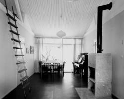 villa Ahnborg Interiör, vardagsrum med piano och öppen spis