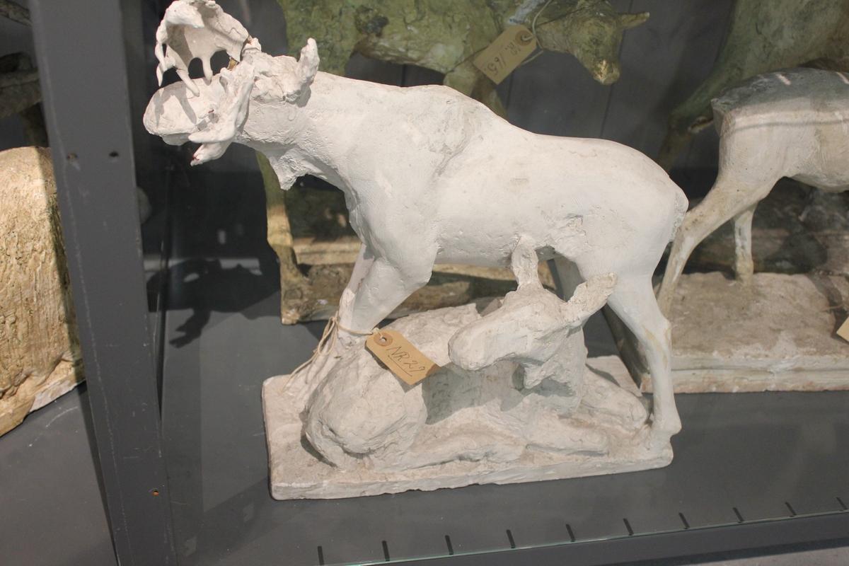 """Skulptur i gips. Tittel: """"ELG"""" fra 1936. Motivet er en stående elg med stort gevir og en liggende elg uten gevir."""